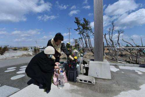 People pray for victims of the 2011 quake-tsunami disaster at a cenotaph in the coastal area of Arahama district in Sendai, Miya