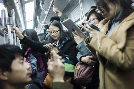 People use their smartphones during the morning rush-hour in Beijing, in November 2014