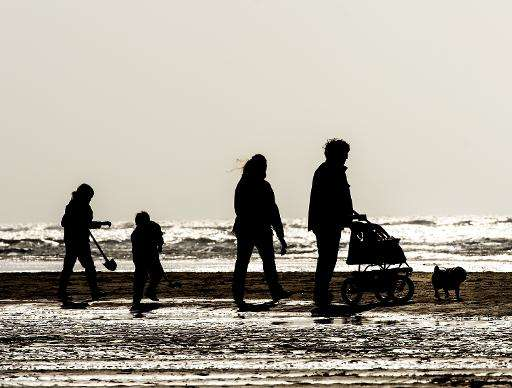 People walk along the beach at Egmond aan Zee on March 8, 2015, in the Netherlands