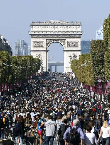 """People walk and cycle along the Champs Elysee Avenue during the """"Car-Free Day"""" event taking place in the French capita"""