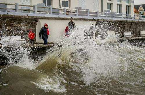 People watch waves crashing onto the Wimereux waterfront, northern France, on February 21, 2015