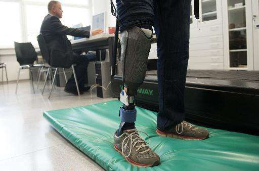 Professor Hubert Egger (L) of Linz University, who created the world's first 'feeling' leg prosthesis, is making tests with Wolf