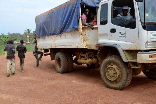 Rubber plantation workers board a truck at the Olam factory in Batouri, at the end of their working day