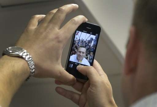 Russian opposition leader Alexei Navalny takes a selfie photograph with the media during a hearing at Moscow's Lyublinsky distri