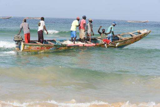 Senegalese fishermen ride a dugout canoe from Kayar beach out to sea, where they are facing competition from Chinese boats fishi