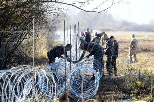 Slovenian soldiers set barbed wire fences on the Slovenian-Croatian border near Rakovec on November 12, 2015