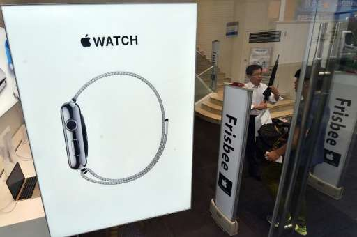 """South Korean customers walk past a signboard of the """"Apple Watch"""" at an Apple shop in Seoul on June 26, 2015"""