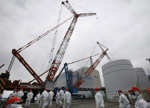 Staff members of Tokyo Electric Power Co. (TEPCO) and the media gather in front of the No. 1 reactor, during a media tour at the
