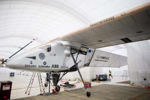 Support crew members stand near the Solar Impulse 2 at Mandalay international airport, Myanmar, on March 20, 2015