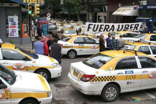 Taxi drivers block the street in front of the hotel where U.S. company Uber is training drivers, in Montevideo, on November 13,