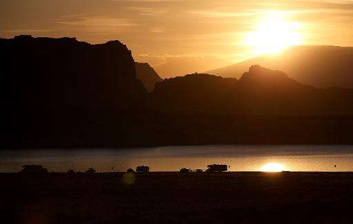 The sun rises over campers at Lake Powell's Lone Rock Camp on March 30, 2015 near Big Water, Utah