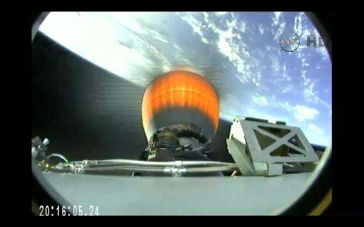 This April 14, 2015 still image from NASA TV shows the engine burn from the SpaceX dragon capsule after separation from the Falc