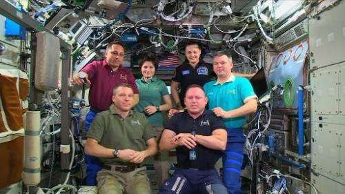 This March 11, 2015 NASA TV image shows Expedition 42 Commander Barry Wilmore (Front-R) handing over control of the ISS to Terry