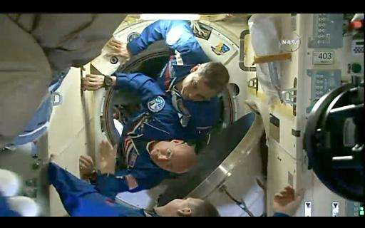 This March 28, 2015 still image from NASA TV shows American astronaut Scott Kelly(bottom) and Russian Mikhail Kornienko(top) ent