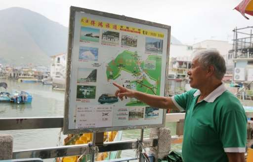 Tour boat operator Wong Yung-kan points out the locations where Hong Kong's famous pink dolphins can be found in the waters arou