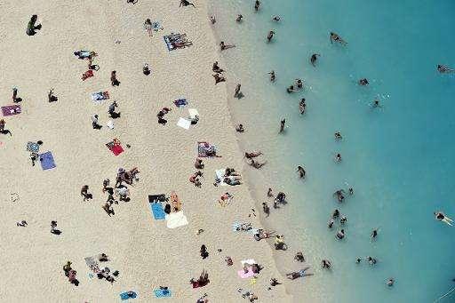 Tourists enjoy the sunshine and the sea at a beach on Zakynthos island, Greece, on June 23, 2014