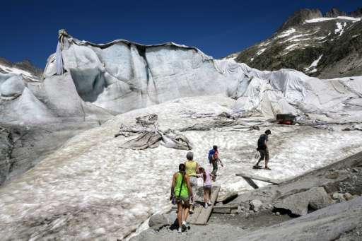 Tourists in July 2015 walk towards an ice cave next to insulating foams wrapping up the Rhone Glacier to prevent it shrinking un