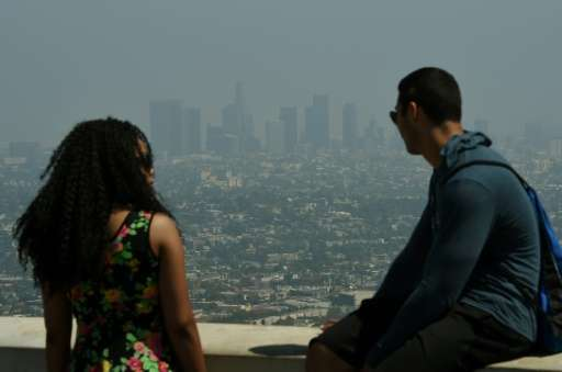 Tourists look out at the Los Angeles skyline as heavy smog shrouds the city