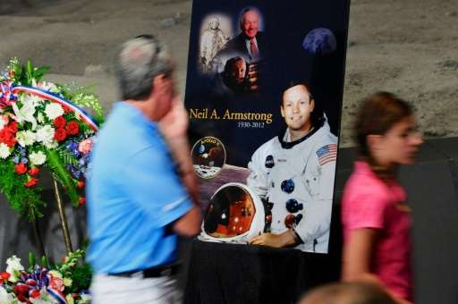 Tourists pass a poster and flowers in honor of former NASA astronaut Neil Armstrong at the Apollo/Saturn V Center, August 31, 20