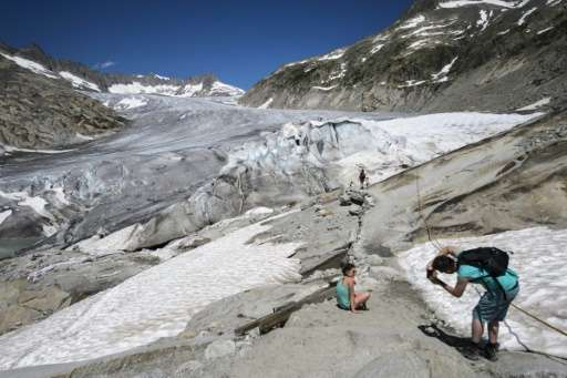 Tourists pose on the Rhone Glacier near Gletsch