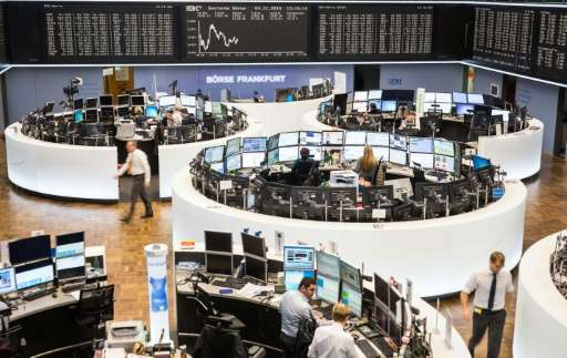 Traders work in front of a board displaying Germany's share index DAX on November 4, 2015 at the stock exchange in Frankfurt am