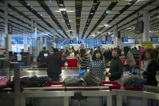 Travellers wait for security check at the Charles de Gaulle airport on December 31, 2012 in Roissy