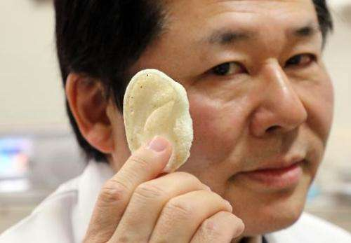 Tsuyoshi Takato, a professor at the University of Tokyo Hospital, displays an artificial ear made of polyactic acid and designed