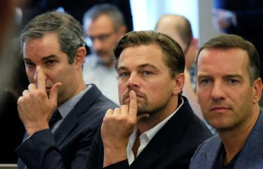 US actor Leonardo DiCaprio (C) sits in the audience during a press conference to announce further business divestment from fossi