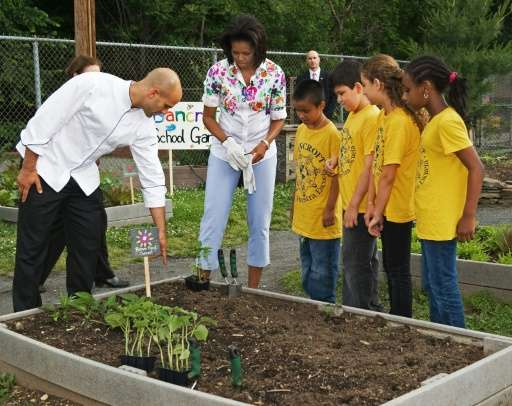 US First Lady Michelle Obama (C) receives some planting advice from White House Assistant Chef Sam Kass (L) while planting veget