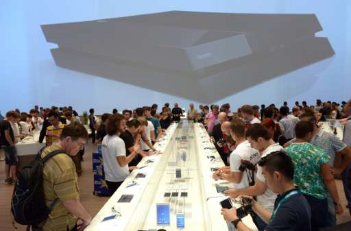 Visitors check out smartphones at the exhibition booth of Sony, during the electronics exhibition IFA, in Berlin, in 2014