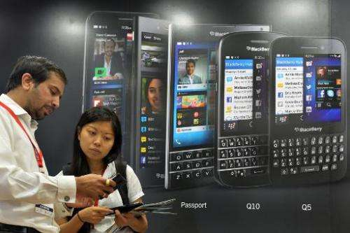 Visitors try out a Blackberry smartphone at the exhibition floor of the 17th BangaloreITE.biz trade fair in Bangalore, India, on