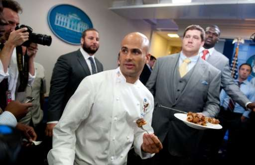 White House Chef Sam Kass (C) serves food to members of the press, prepared with help from Zach Strief (R), a member of the 2010