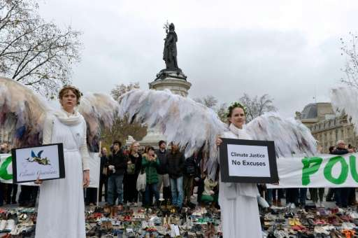 Women dressed as angels holds signs at the Place de la Repubique on November 29, 2015, in Paris, on the eve of the official open