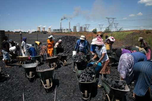Women from Masakhane settlement fill their wheel barrows with free coal provided by the nearby mine in Emalahleni