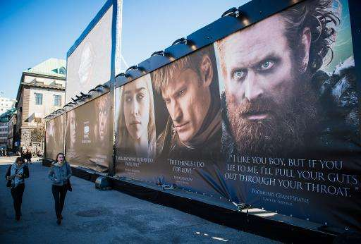 Women walk past an advertising poster to promote the HBO American fantasy drama television series Game of Thrones outside the In