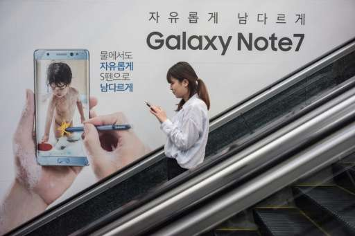 A woman looks at her mobile phone as she rides an escalator past an advertisement for Samsung's Galaxy Note 7 device in Seoul on