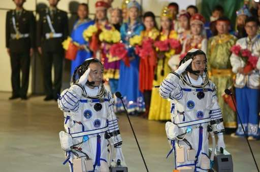 Chinese astronauts Jing Haipeng (L) and Chen Dong, pictured at their send-off ceremony, spent 33-days orbiting the earth carryin