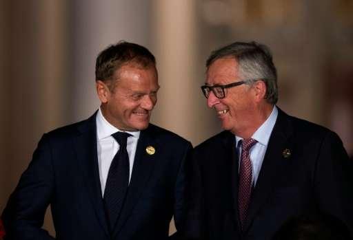 European Council President Donald Tusk (L) talks with President of the European Commission Jean-Claude Juncker as they walk acro