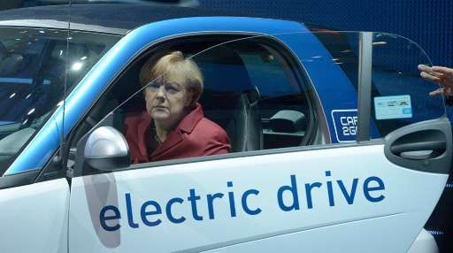 German Chancellor Angela Merkel sits in an electric car at the Daimler subsidiary car2go booth at the 2013 Frankfurt car show