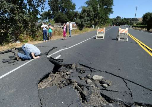 Local resident inspects a buckled highway outside of Napa, California, after earthquake struck the area in the early hours of Au