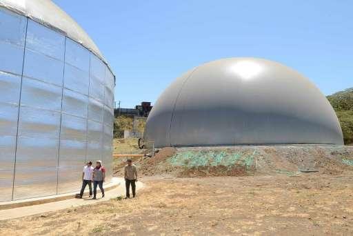 People walk past an 8,000 cubic-meter biodigestor at El Arreo slaughterhouse in Belen, Costa Rica