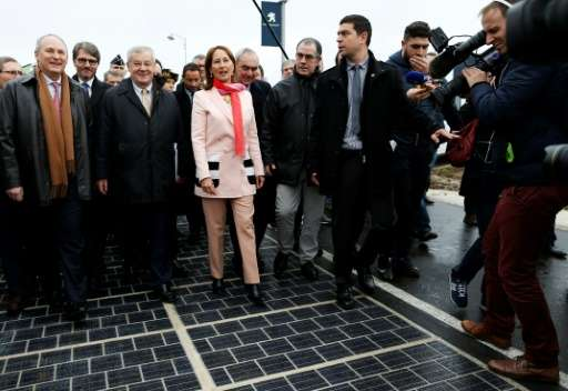 Segolene Royal and other officials walk on a solar panel road at its inauguration in Tourouvre, on December 22, 2016