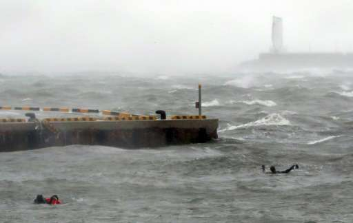 South Korean coast guards try to rescue crew members of a stranded passenger ship in the aftermath of typhoon Chaba in the south