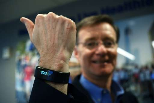United Healthcare New York CEO Michael McGuire poses wearing a special activity tracker at his office in New York on March 24, 2
