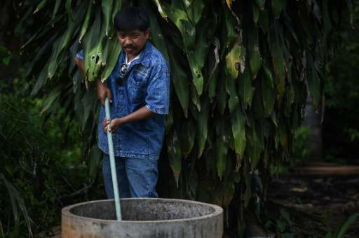 Wisut Janprapai feeds waste to his bio-gas balloon outside his home in Pa Deng village
