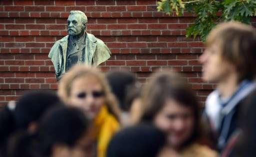 People walk past a statue of Swedish inventor Alfred Nobel at the Karolinska Institute in Stockholm