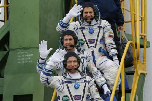 Russian cosmonauts Sergei Ryzhikov (bottom) and Andrei Borisenko (top) and US astronaut Shane Kimbrough wave as they board the S