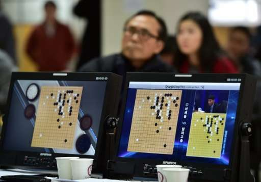South Korean Go game fans watch a television screen broadcasting live footage of the Google DeepMind Challenge Match in Seoul on