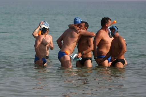 Participants greet each other as they arrive at the Israeli shore during a 17-kilometre swim from Jordan to Israel across the De