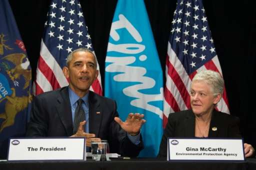 US President Barack Obama (L) speaks with EPA Administrator Gina McCarthy (R) during a meeting at the Food Bank of Eastern Michi